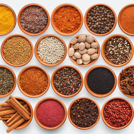 Spices assortment background. Variety of seasonings and condiments in clay bowls isolated on white, top view