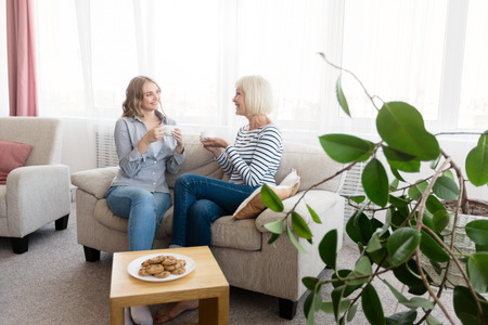 Happy mother and daughter talking and drinking coffee in living room, copy space
