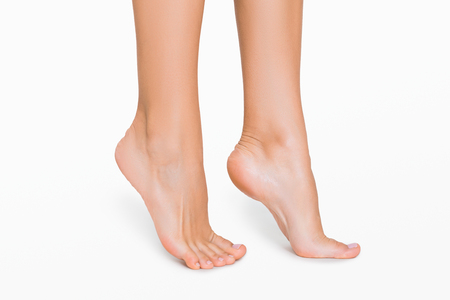 Woman standing on tiptoes. Perfect female feet with smooth skin, side view, isolated on white background