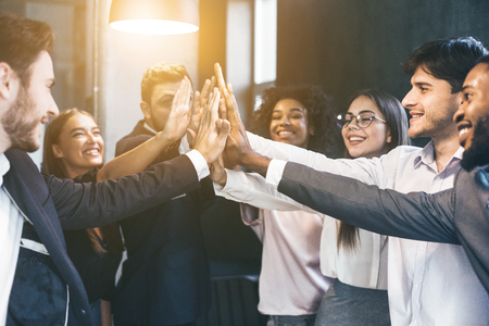 Happy multiracial business team giving high fives gesture , celebrating success