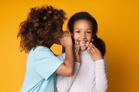 Cute girl telling secret her friend on yellow background Banco de Imagens