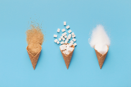 Wafer ice cream cones with different sugar kinds on blue background, top view