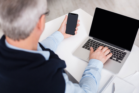 Mature man using laptop and smartphone with blank screen back view, copy space, mockup Stockfoto