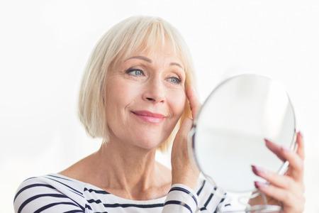 Senior vrouw die haar zachte gezichtshuid aanraakt, thuis in de spiegel kijkt Stockfoto