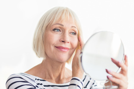 Senior woman touching her soft face skin, looking in mirror at home