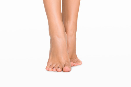 On tiptoe. Caucasian womens feet isolated on white background Stock Photo