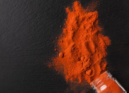 Chilli powder scattered from bottle on black background, top view Stock fotó