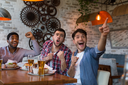 Friends watching football game on TV and drinking beer in bar