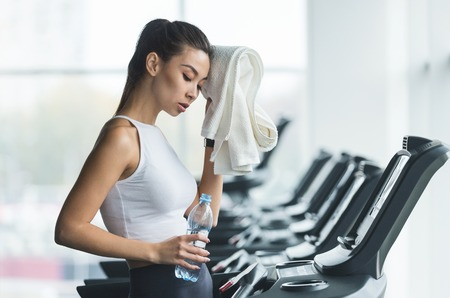 Woman tired and having rest after running on treadmill in modern gym