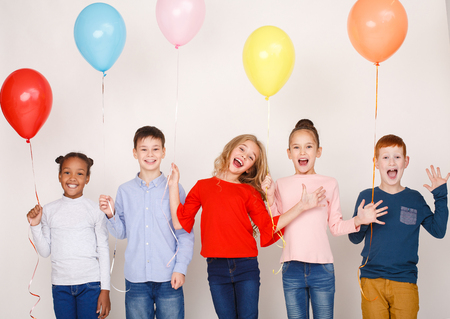 Happy children having fun with colourful balloons over light wall