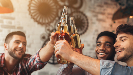 Friends celebrating meeting, clinking bottles of beer in bar