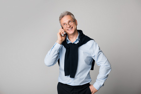 Happy mature man talking on phone over grey background Stock Photo
