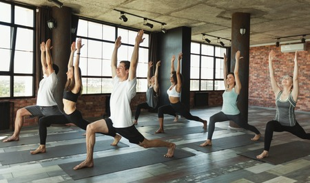 Group of young sporty people practicing yoga, standing in Warrior one pose, Virabhadrasana I pose, working out in loft studio.