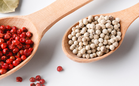 Red and white pepper in wooden spoons on white background Stok Fotoğraf