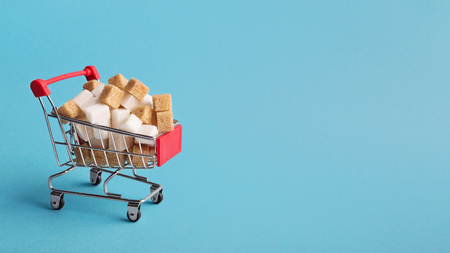 Tiny shopping cart with sugar cubes on blue background, panorama, copy space