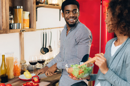 Food cooking together. Young smiling african-american couple preparing vegetable salad in kitchen, copy space 免版税图像