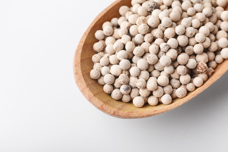 Whole white peppercorns wooden spoon on white background. Recipe concept, copy space