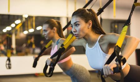 Mujeres entrenando brazos con correas de fitness trx en el gimnasio Foto de archivo