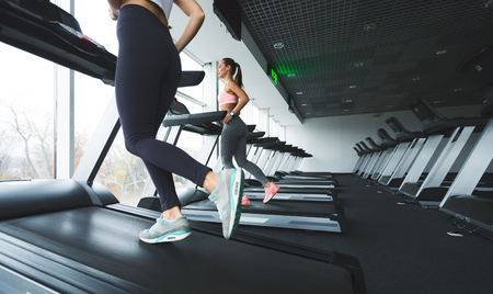 Women running up on treadmill in the gym, copy space
