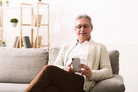 Hombre maduro con smartphone, navegar por internet, sentado en el sofá en casa, espacio de copia