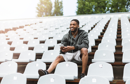 Hadsome smiling man sitting on stadium seats, listening music, relax after workout