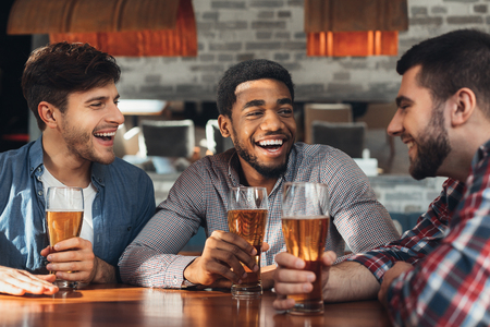 Multiracial men drinking beer and talking, sitting in modern bar