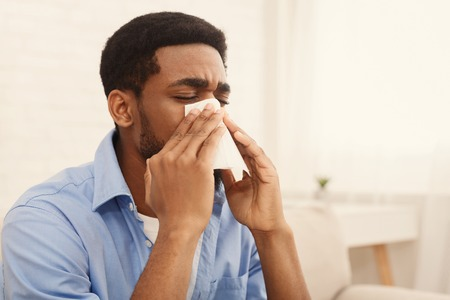 Seasonal flu. African-american man man has runny nose at home, blowing his nose into paper napkin at home, copy space