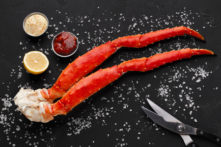 Gourmet seafood. Cooked king crab legs served with eating tools and sauces on black salted table, top view