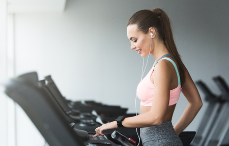 Woman adjusting speed on treadmill, doing cardio workout in sports club Banco de Imagens