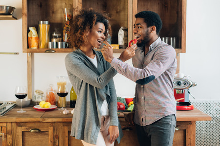 Sharing food. Loving african-american couple feeding each other with vegetables in kitchen Banque d'images - 115153968