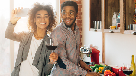 Cooking boyfriend is great. Happy african-american woman making selfie with her man in kitchen, panorama, copy space