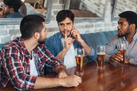 Man asking for silence, talking on phone, sitting in bar with friends