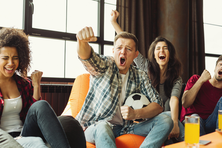 """Football fans watching a match on tv, screaming """"Goal!"""" Yes! Goal! Winners! concept"""