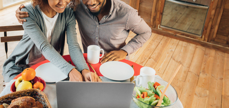 Order food online. Young african-american couple in kitchen ordering dinner from restaurant, searching menu on laptop, panorama, copy space Stock Photo
