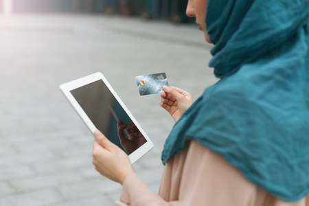 Muslim woman wearing hijab using tablet and holding credit card. Protect your personal data concept
