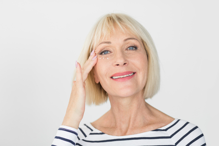 Beautiful woman applying anti-wrinkle cream, looking at camera over light background Imagens