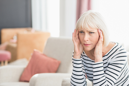 Woman suffering from headache, sitting on sofa at home, copy space