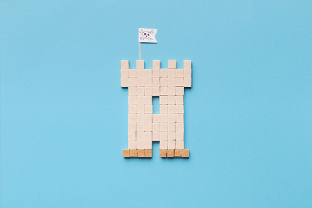 Threat of sugary eating. Pirate castle made of sugar cubes on blue background, top view