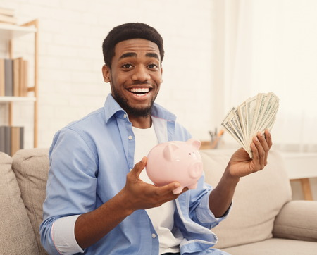 Unexpectable profit. Excited african-american guy holding piggybank and lots of hundred dollar bills at home