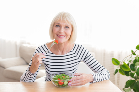 Happy senior lady eating fresh green salad, having rest at home