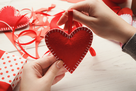 Valentines day diy, wedding or other holiday decorations background. Handmade gift greeting heart pillow creating, cut and sew, handmade tools on white wood, copy space
