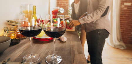 Young couple preparing dinner together in kitchen, two glasses of red wine on foreground, panorama, copy space