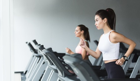 Fit women doing cardio workout, running on treadmill in gym, copy space