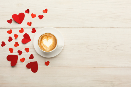 Valentine background with red handmade paper hearts and hot coffee cup on white rustic wooden planks. Happy lovers day card mockup, copy space, top view