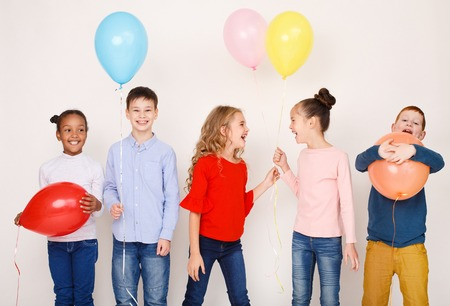 Children with colourful balloons, having fun over light wall