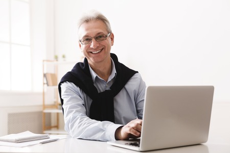 Happy senior man using computer and looking at camera, working at home office