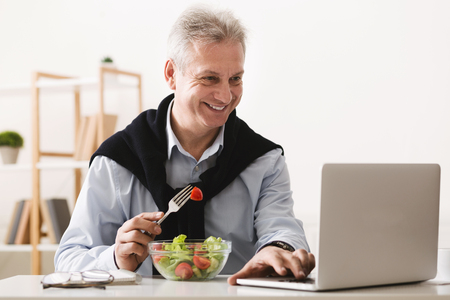 Mature businessman eating salad and working on laptop at home office