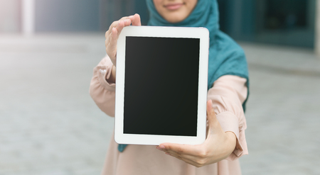Muslim woman holding tablet in front of face. Technology for life concept, copy space Imagens