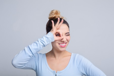 Just for fun. Woman gesturing ok sign near her eye against grey background Stock Photo