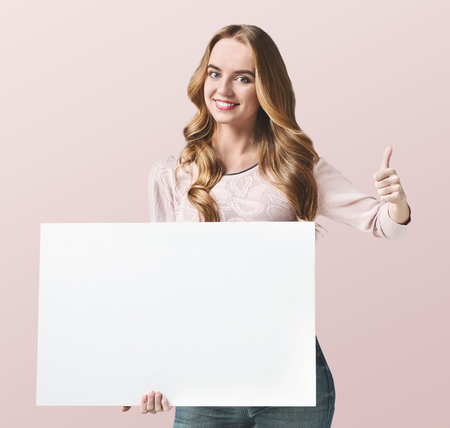 Happy girl holding a sheet of paper in her hand with thumbs- up gesture. Place for your text, concept, copy space, isolated